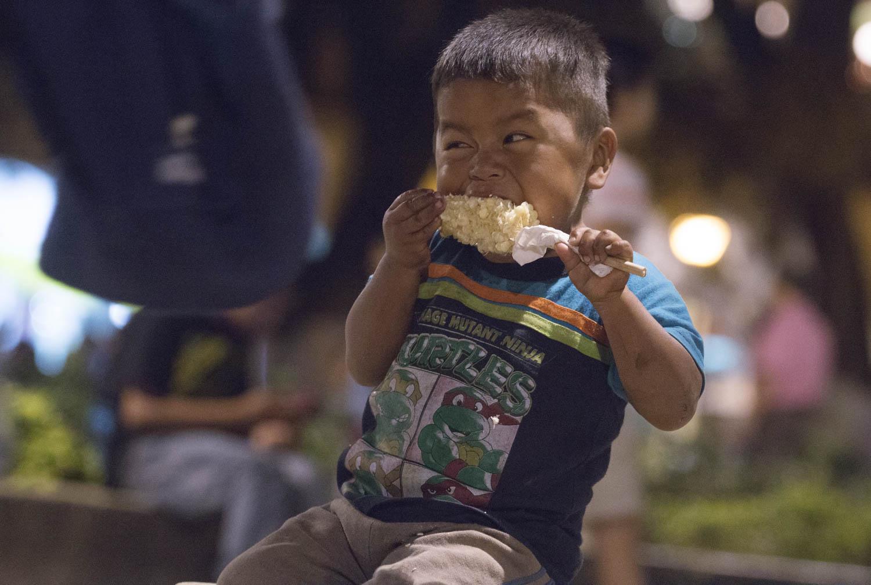 OAXACA, OAXACA, 16NOVIEMBRE2015.- Niños triquis originarios de San Juan Copala y que viven en los corredores del palacio de gobierno comen un un elote en el zócalo de la ciudad de Oaxaca.  Foto: Arturo Pérez /Cuartoscuro.com
