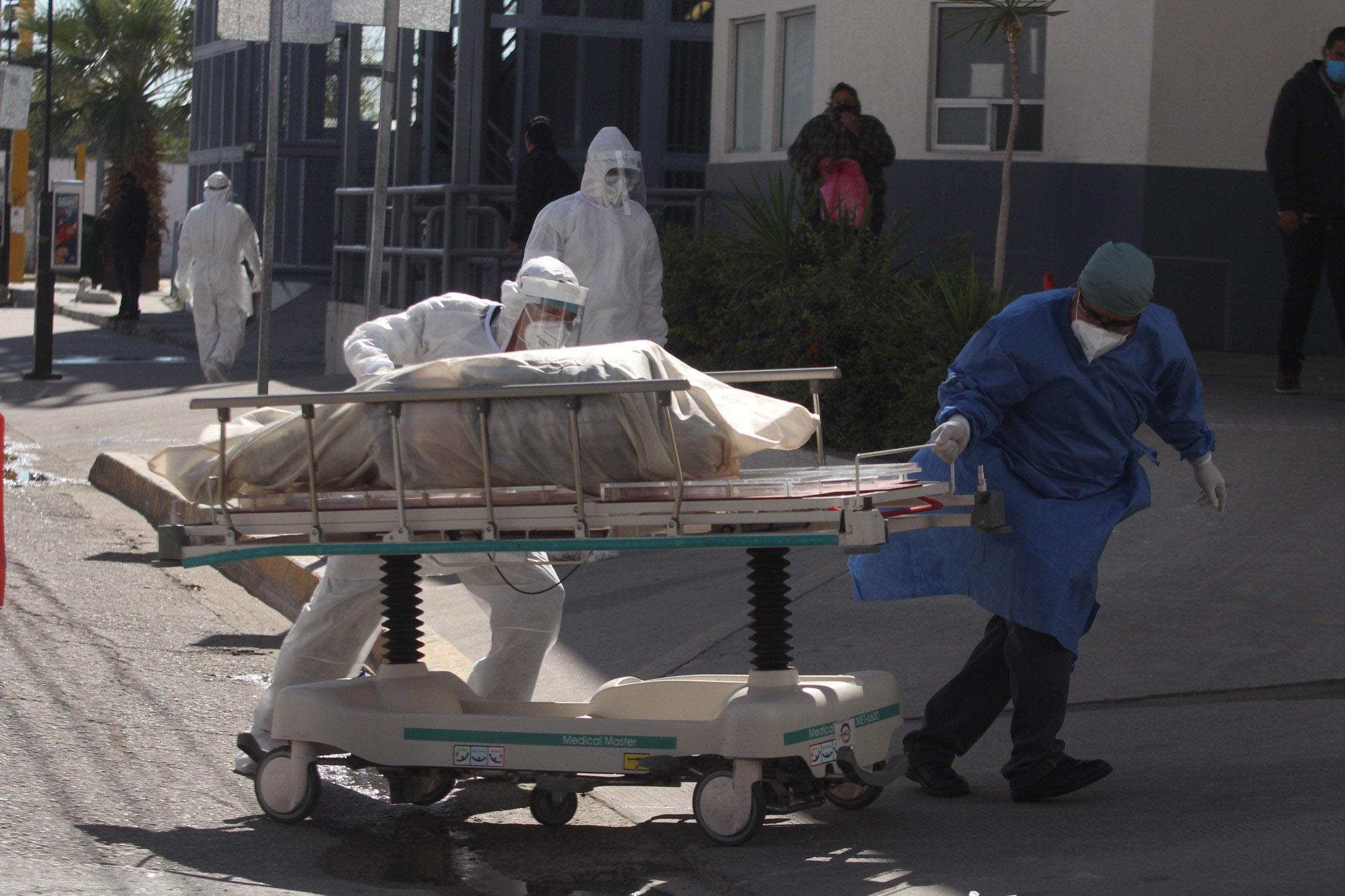 Personal médico del Hospital General de Ciudad Juárez traslada el cuerpo de una persona que presuntamente murió por Covid-19.